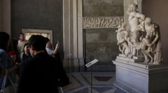 Tourists taking photos of a statue, the Laocoon. Stock Footage