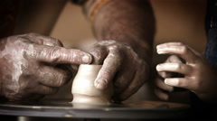 Male potter teaches his little pupil to make a pot from scratch Stock Footage