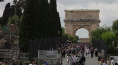 View of Arch of Titus and tourists seen walking near the Colosseum. Stock Footage