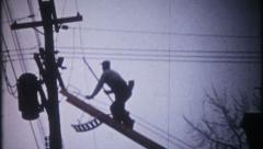 2364 - power company worker climbs ladder, repairs line -vintage film home movie Stock Footage