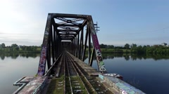 Stunning cinematic low aerial of metal train bridge with graffiti. Stock Footage