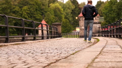 Lonely man and a couple walk by the cobbled thoroughfare - stock footage