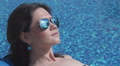 Close-up of woman sunbathing near pool, blue water background Footage