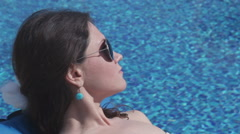 Young beauty suntanning near water, sky reflection in sunglasses - stock footage