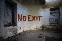 text no exit on the dirty old wall in an abandoned ruined house - stock photo