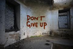 text dont give up on the dirty old wall in an abandoned ruined house - stock photo