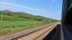 Train driving in farmlands and mountains Stock Footage