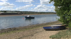 Small Boats on the Water and Riverbank at Low Tide on River Axe Seaton Devon - stock footage