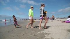 Two girls wearing shorts, walking on beach, bare feet Stock Footage