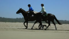 Two females riding horses along white sanded beach Stock Footage