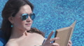 Pretty female in sunglasses reading book on the beach, leisure HD Footage