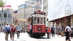 Taksim Tram trundles along istiklal street and crowded people. Istanbul, Turkey Stock Footage