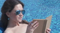 Beautiful woman relaxing with book by pool, sunbathing at beach Footage