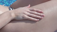 Woman on beach applying spf skincare lotion, rubbing her body Stock Footage