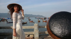 girl poses in vietnamese hat on embankment - stock footage