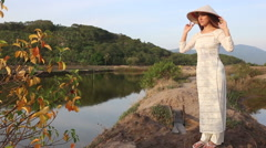 Blonde girl in vietnamese costume and hat poses between ponds Stock Footage