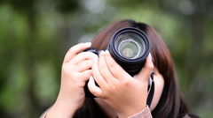Young woman takes pictures with DSLR camera. - stock footage