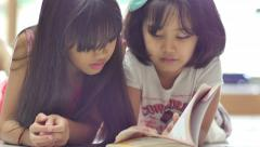 Little Asian child reading book in library together Stock Footage