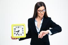 Businesswoman holding wall clock and looking on wristwatch Stock Photos