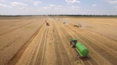 Aerial view of wheat field width many combine harvesters. Stock Footage