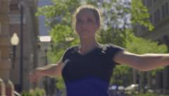 Stock Video Footage of Determined Ballerina Practices Pirouettes (Spins) In City Square, Closeup (4K)