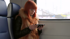 Redhead girl reads an sms in the train Stock Footage