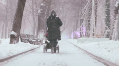 Mother walking  with baby carriage during snowing Stock Footage