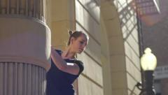 Stock Video Footage of Ballerina Stretches Against Building, Practices Leg Extension (Slow Motion)