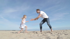 Father Spinning Daughter Round on the Beach - stock footage