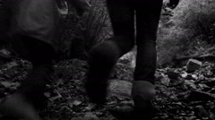 Black and white footage: mother and son climbing their way up to the waterfall Stock Footage