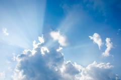 Stock Photo of Nice sun beam shining through clouds sky