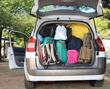 car overloaded with suitcases for travel - stock photo