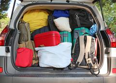 trunk of a car overloaded with suitcases  for family travel - stock photo