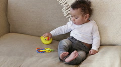 Little boy playing with toys on the sofa Stock Footage