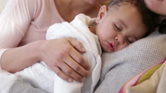 Female couple with sleeping son at home Stock Footage
