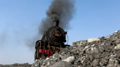 Steam locomotive stopping on mine coal hill,emitting black smoke Stock Footage
