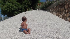 Child plays with stones on heap of pebbles Stock Footage