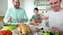 Same sex male couple having dinner with their son. They are serving vegetable Stock Footage