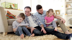 Male couple helping their children with homework Stock Footage