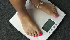 Female barefoot legs stepping on digital floor scales Stock Footage