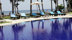 The empty pool with bright blue water and chairs for rest Stock Footage
