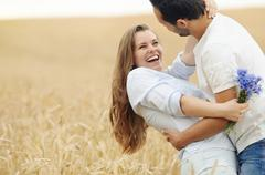 happy young couple having fun in summer field - stock photo