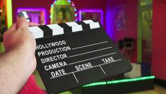 Movie Clapperboard Infront Of Multicolored Stage With Flashing LED Lights Stock Footage