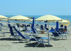 Sunloungers and parasol on the beach during the hot summer Stock Photos