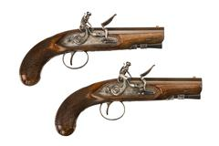 Flintlock pistols pair short barreled isolated on white - stock photo