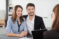 Happy Couple Talking to Realty Agent in the Office - stock photo