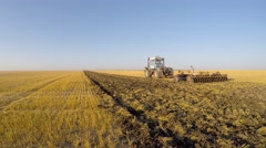 The tractor works the soil disc cultivator. Eastern Ukraine. - stock footage