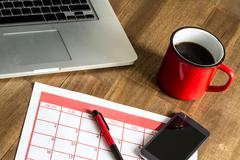 Organizing monthly activities in the calendar - stock photo