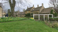 Footbridge over River Eye in Lower Slaughter Village in the Cotswol - stock footage
