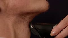 Young man shaving his beard off with an electric shaver Stock Footage